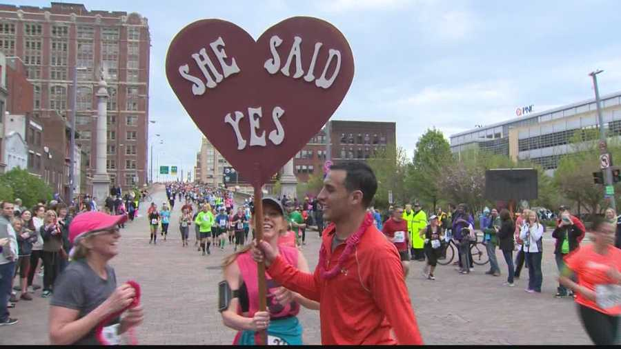 Joe Sidhom holds a sign to tell everyone about Katie Mulkern's answer to his marriage proposal at the Pittsburgh Marathon.