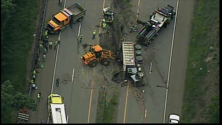 Sky 4 flew over the crash site, where a white car was heavily damaged and the coal truck was overturned. Machinery was brought in to right the truck and a backhoe was clearing debris from the roadway.