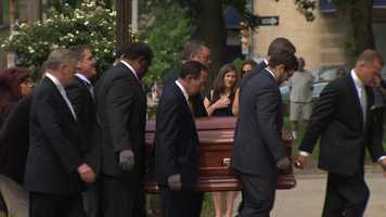 Pallbearers carry Chuck Noll's casket into Saint Paul Cathedral in Oakland.