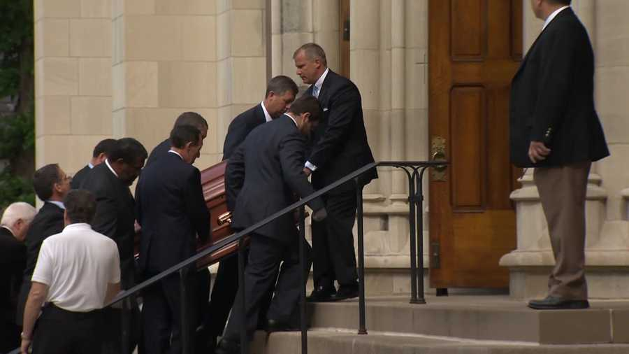 Pallbearers carry Chuck Noll's casket up the steps of Saint Paul Cathedral in Oakland.