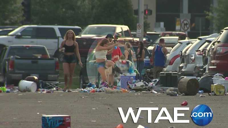 WTAE video shows a young woman kicking a bag full of garbage around a trash-filled parking lot near Heinz Field before a Luke Bryan concert.