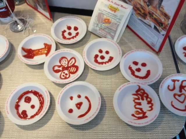 Pictures drawn in ketchup on plates at Johnny Rockets.