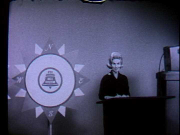 Eleanor Schano, reading in front of a Bell System logo.