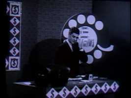 "In this photo, ""Dialing for Dollars"" host Del Taylor calls a viewer at home and asks him for the correct ""count"" and ""amount"" to win a cash prize."