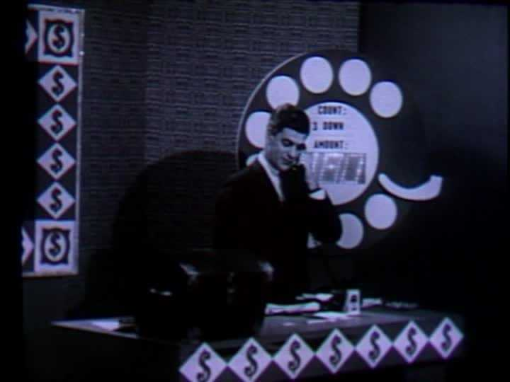 """In this photo, """"Dialing for Dollars"""" host Del Taylor calls a viewer at home and asks him for the correct """"count"""" and """"amount"""" to win a cash prize."""
