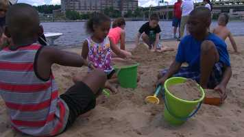 """Beach 'Burgh"" is an area with sand, palm trees and kids' toys on the Allegheny River steps at the Regatta."