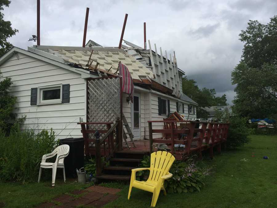A woman was standing on steps outside a home on Henderson Road in Jackson Center, Mercer County, when strong winds flipped a porch roof onto the roof of the house.