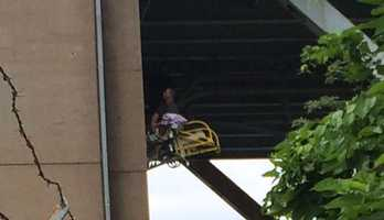 A first responder onto of a ladder truck's main ladder checks on the trapped child underneath the superstructure of the bridge.