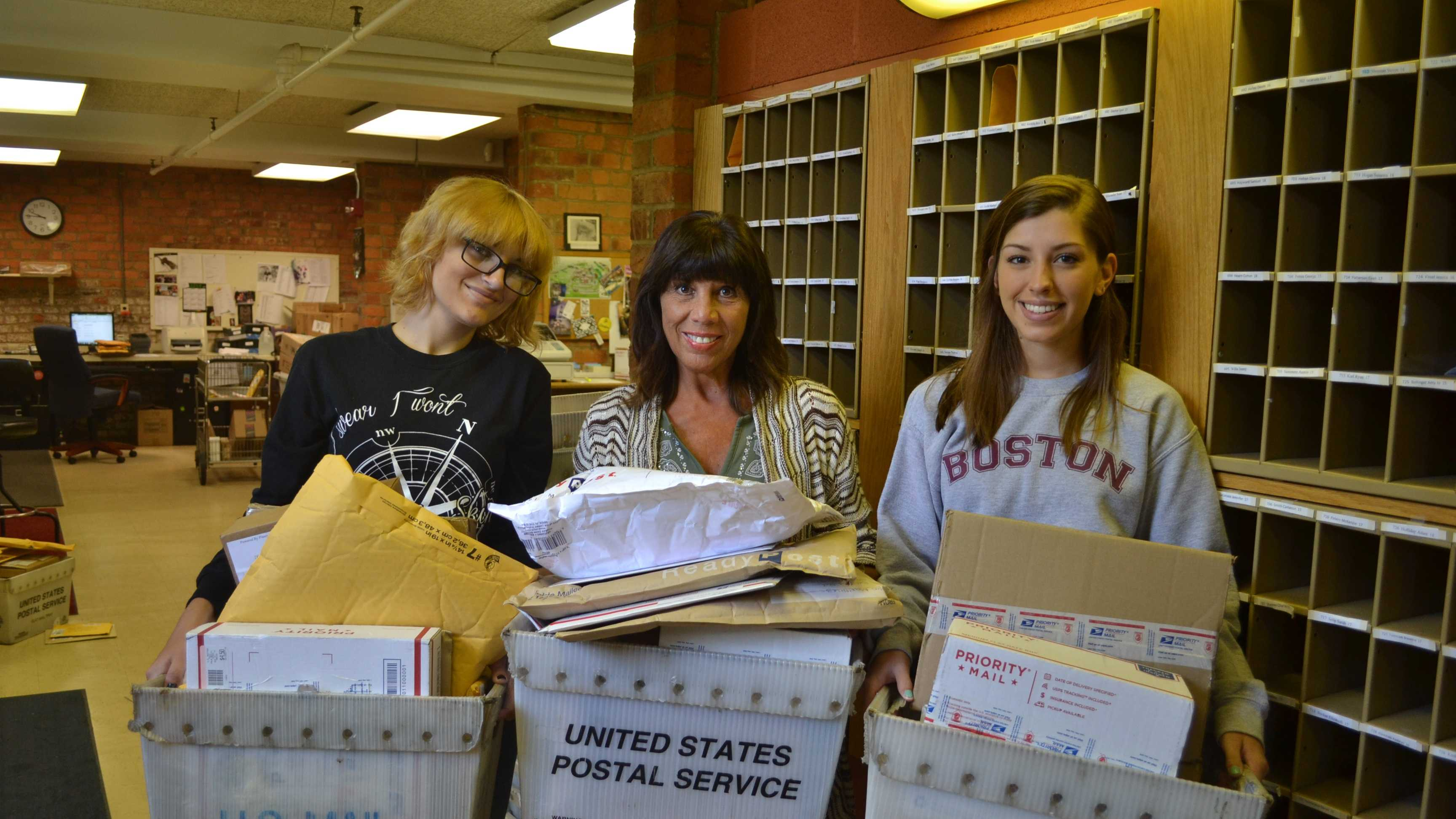 Student assistant Katie Nemchik, assistant manager Maria Schifano and student assistant Ally Frye sort the daily stacks of incoming mail for Steelers players during training camp at Saint Vincent College.