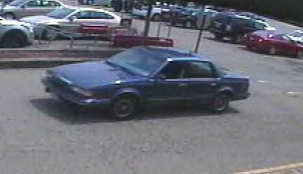 The car is described as a blue 1990s-model Buick Century with an unknown type of vanity plate on the front. The robber is described as a white man in his mid-20s with a thin build, black hair (medium to short) and a dark goatee.