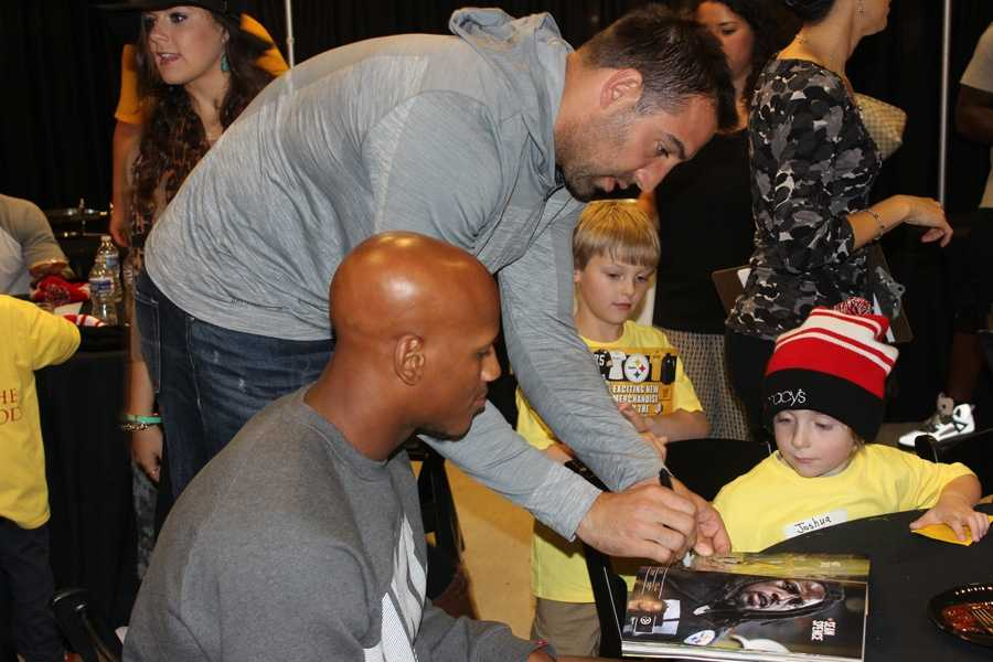 Matt Spaeth signs his autograph in the kids' Steelers yearbooks