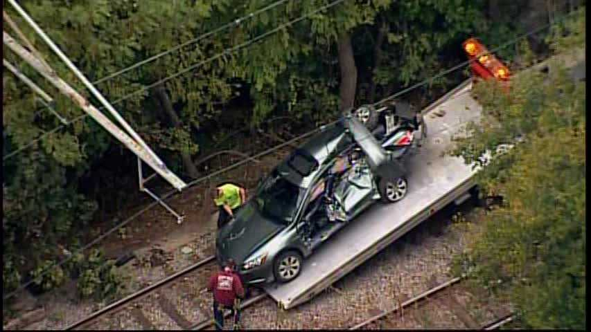 A flatbed tow truck drove onto the T tracks to remove the damaged car.