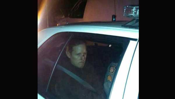 Eric Frein sits in the back of a police car after being arrested.