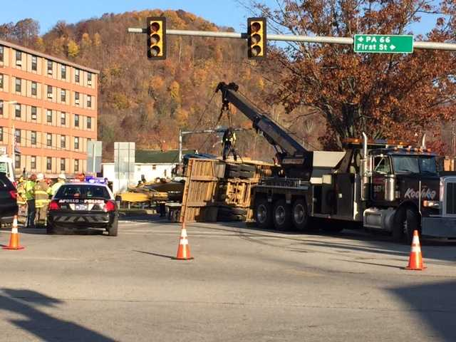 An emergency dispatcher says a car's driver was briefly trapped when a excavator toppled onto his vehicle near a western Pennsylvania bridge.