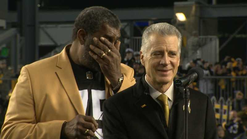 Joe Greene becomes emotional during a ceremony to retire his No. 75 jersey. Steelers President Art Rooney II stands next to him.