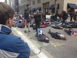 """People lie down on Smithfield Street in a """"die-in"""" to protest the decision not to indict a police officer in the death of Eric Garner."""