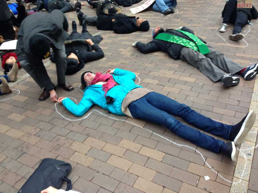 "Demonstrators trace chalk outlines around people lying on Grant Street as part of a ""die-in"" protest over the grand jury's decision in the Eric Garner case."