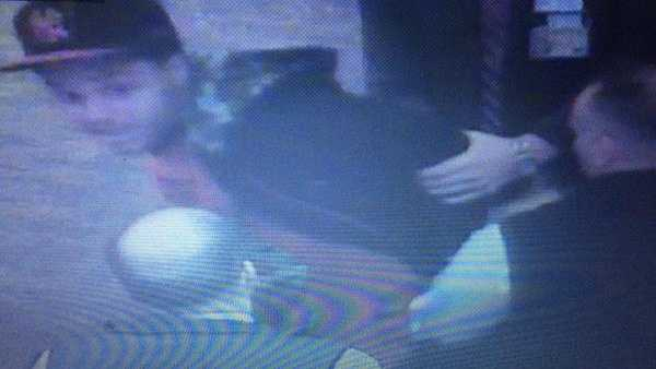 A security camera image of Dustin Andrejco-Jones being handcuffed.