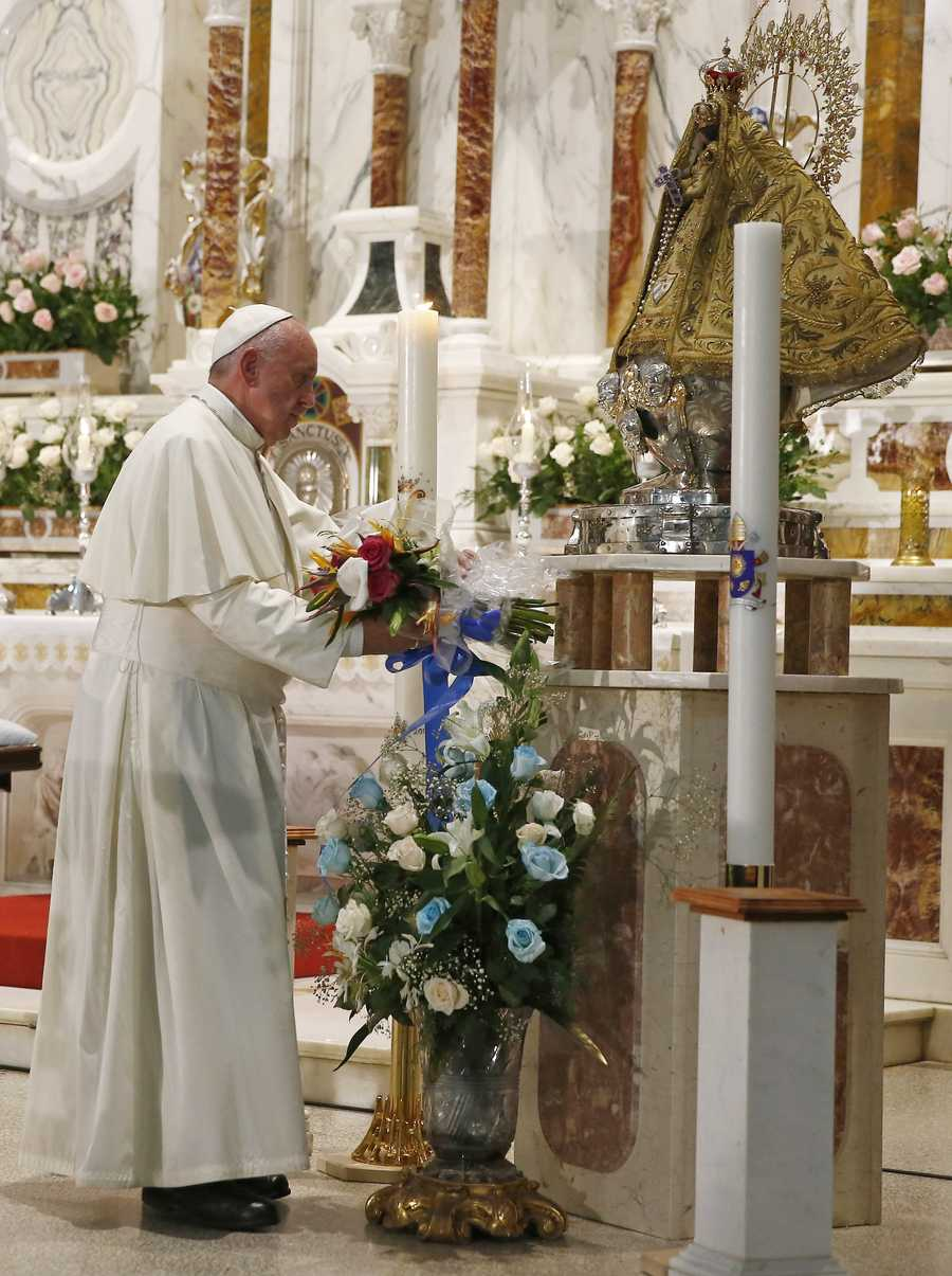 Pope Francis places a bouquet of flowers before the statue of the Virgin of Charity of Cobre, in El Cobre, Cuba, Monday.