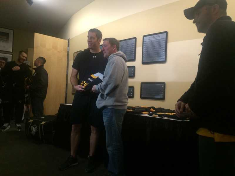 Rob Scuderi hands a personalized Penguins jersey to a veteran.