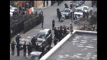 The casket, draped in a flag, is carried inside for Officer Lloyd Reed's funeral service.