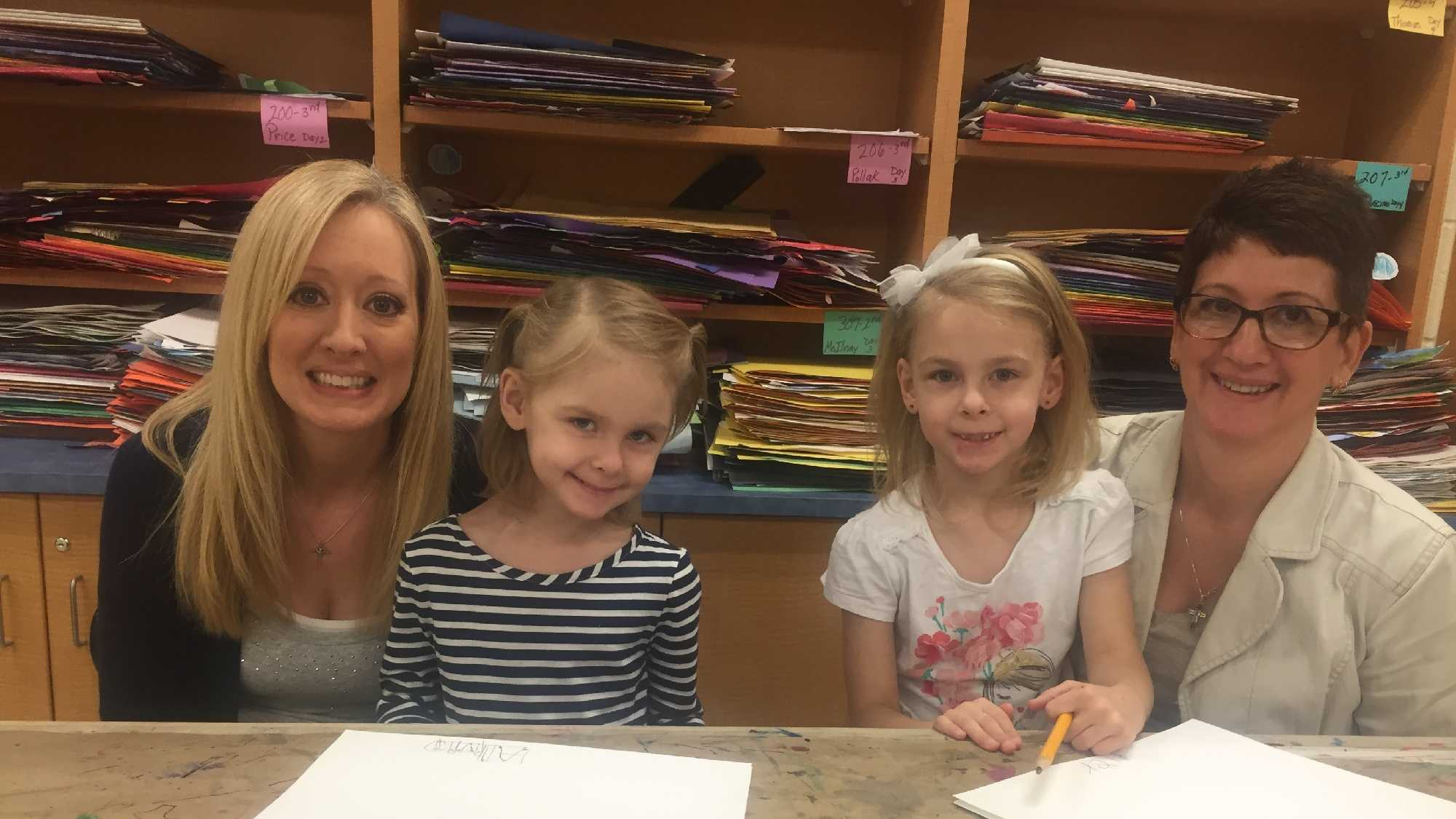 Alivia Johnson (left) and Riley Johnson (right), both 6, are pictured here with their teacher's aides at Stanwood Elementary School.