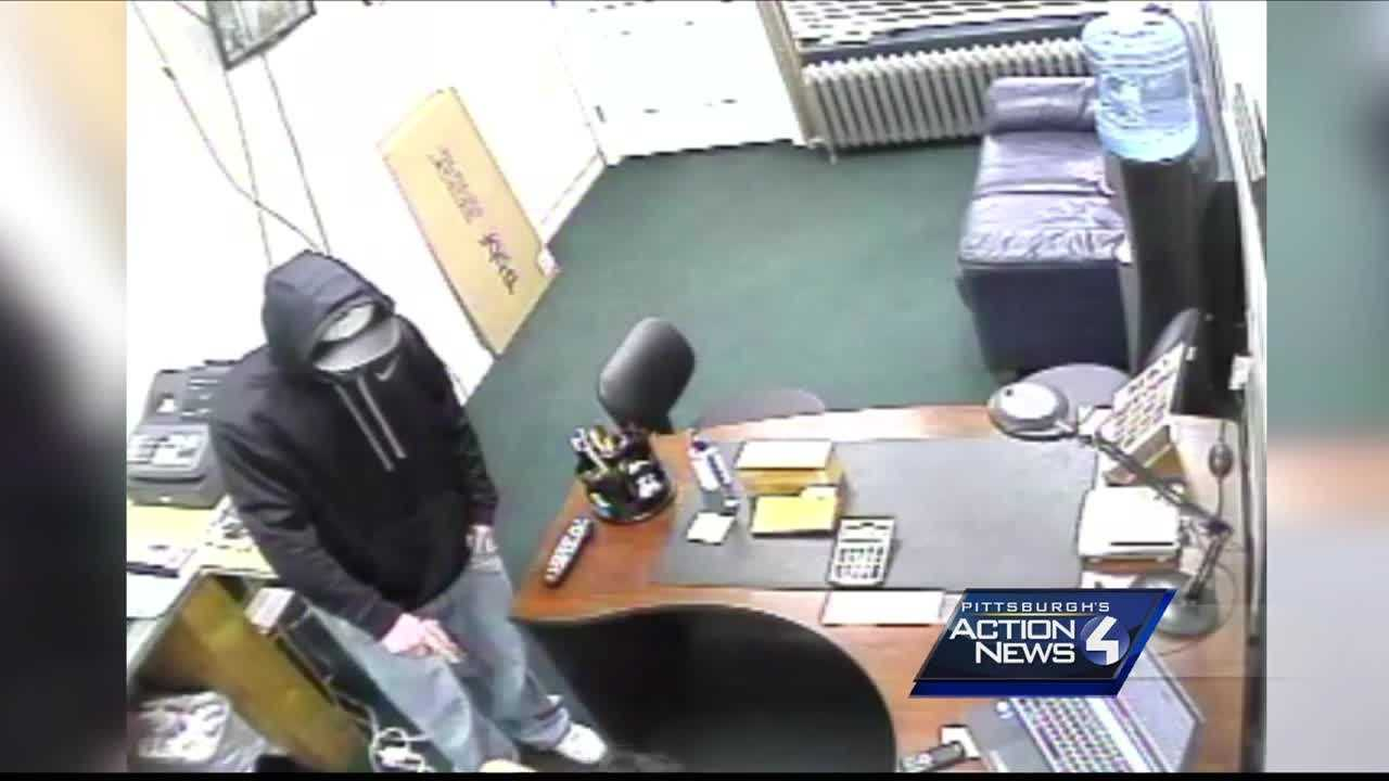 This surveillance image shows a robber pointing a gun at an employee at Cash For Gold on West Liberty Avenue in Dormont.