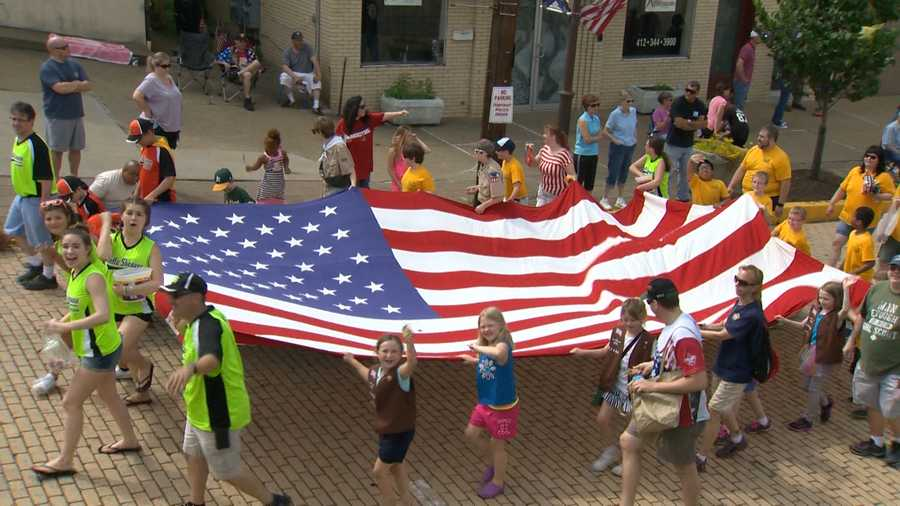 A giant U.S. flag was carried by several children as they marched down Willow Avenue toward Castle Shannon Boulevard.