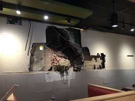 Emergency responders spent several hours working to rescue the man, including cutting holes through the wall of a Qdoba restaurant.
