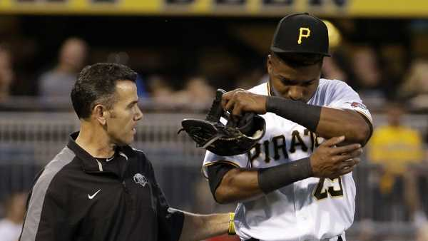 Pittsburgh Pirates left fielder Gregory Polanco (25) walks off the field with a team trainer after running into the outfield wall trying to catch a fly ball hit by Washington Nationals' Bryce Harper in the first inning of a baseball game in Pittsburgh, Friday, Sept. 23, 2016. Harper ended up with a double on the play.