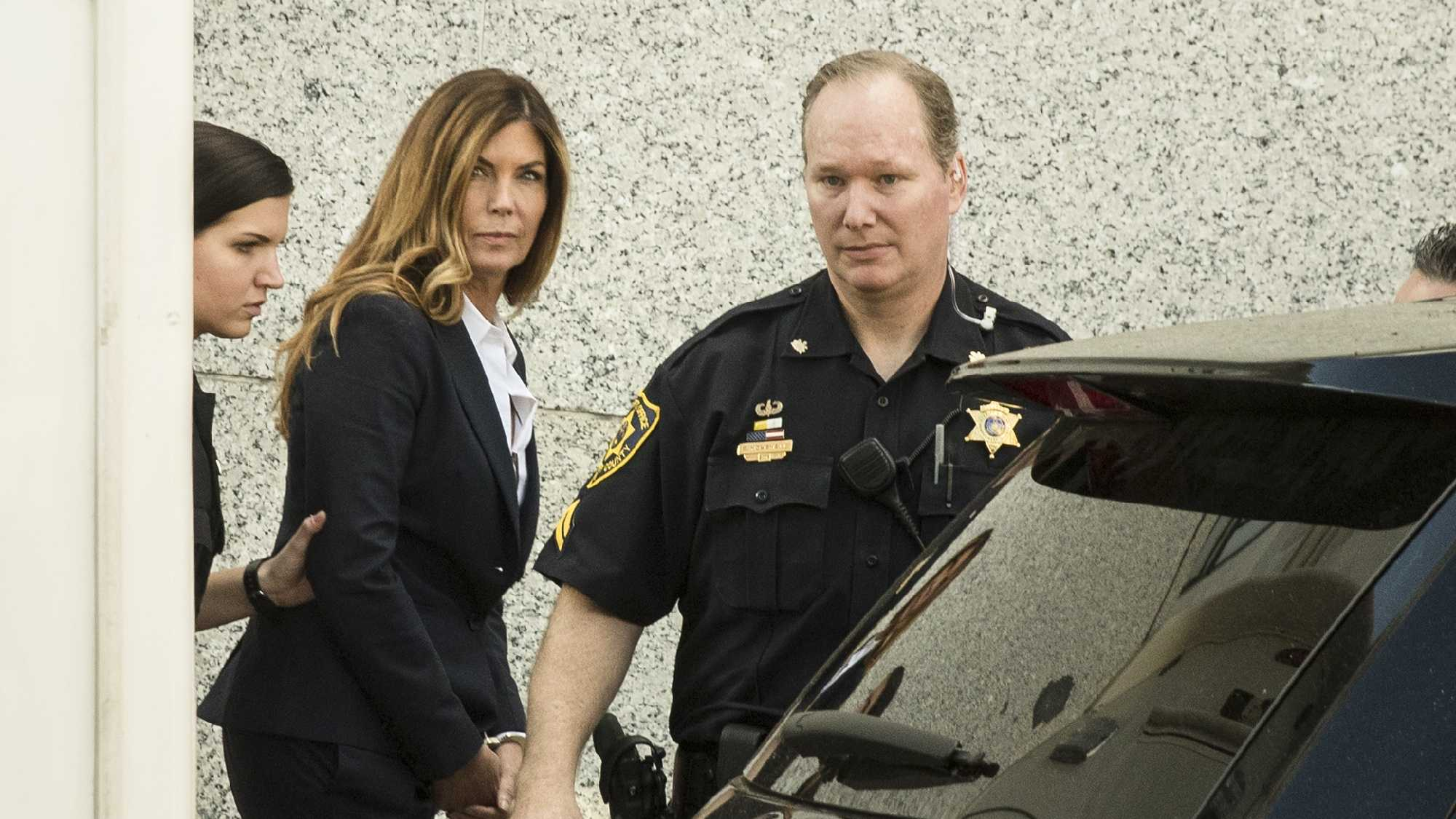 Former Pennsylvania Attorney General Kathleen Kane is escorted from Montgomery County courthouse after her sentencing hearing in Norristown, Pa, Monday, Oct. 24, 2016.