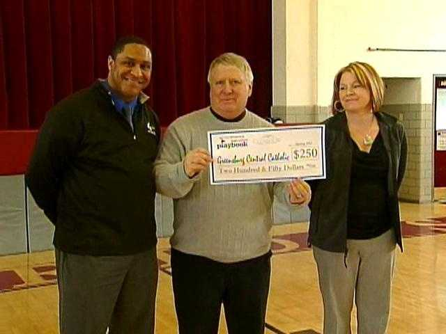 High School Playbook's Josh Taylor presents a check to Greensburg Central Catholic principal Don Favero and assistant principal Denise Myers