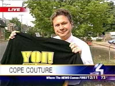 """Channel 4 Action News reporter Bob Mayo holding a shirt with Cope's signature catchphrase: """"Yoi!"""""""