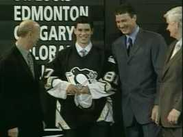 Sidney Crosby dons a Penguins sweater and is congratulated by general manager Craig Patrick, owner Mario Lemieux and team president Ken Sawyer.