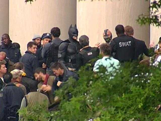 "Batman and the villain Bane (wearing mask over nose and mouth, next to actor in SWAT vest) on ""The Dark Knight Rises"" movie set in Oakland."