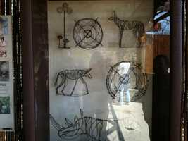 These are pieces of artwork made out of snares by villagers in Zimbabwe. Snares are used by poachers, and kill and maim the dogs. The villagers find the snares remove them and make conservation artwork to sell.