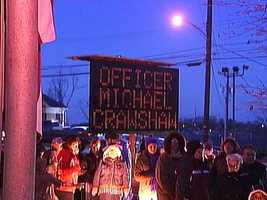 A roadside sign bearing slain Penn Hills police officer Michael Crawshaw's name stands where mourners gather for a candlelight vigil