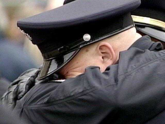 Police officers hug each other at the ceremonial final roll call for Michael Crawshaw in Penn Hills.
