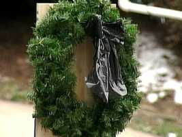 A black ribbon is tied on a wreath on Johnston Road to remember Penn Hills Police Officer Michael Crawshaw.