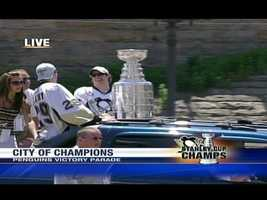 Sidney Crosby and Marc-Andre Fleury show off the Stanley Cup along the downtown Pittsburgh parade route.