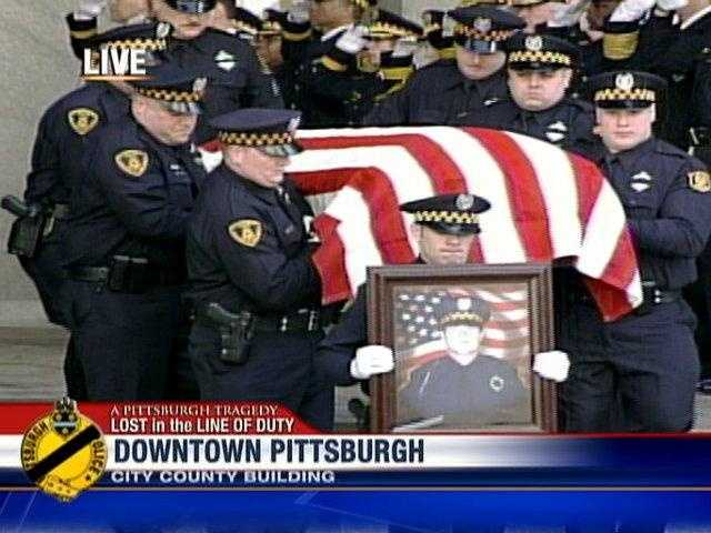 The casket carrying Officer Stephen Mayhle leaves the viewing.
