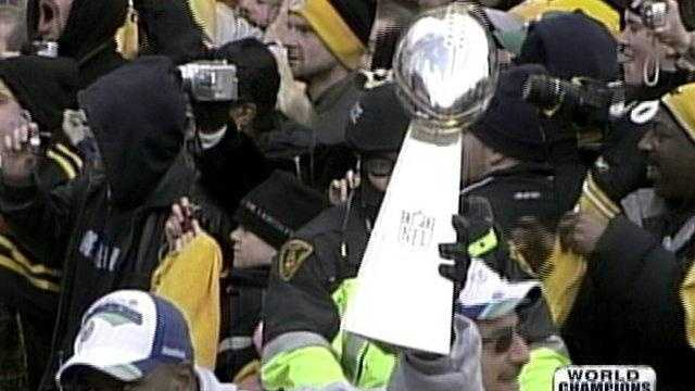 James Harrison holds the Lombardi Trophy at the Super Bowl XLIII victory parade.