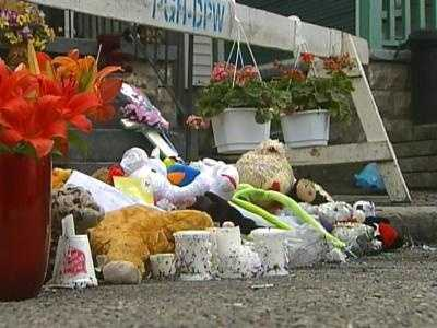 Flowers, photographs and an oversized condolence card were on display in a makeshift memorial outside the burned house.