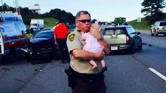 Jefferson County Sheriff's Deputy Ric Lindley cradles an infant on the scene of a wreck near Leeds Tuesday morning.