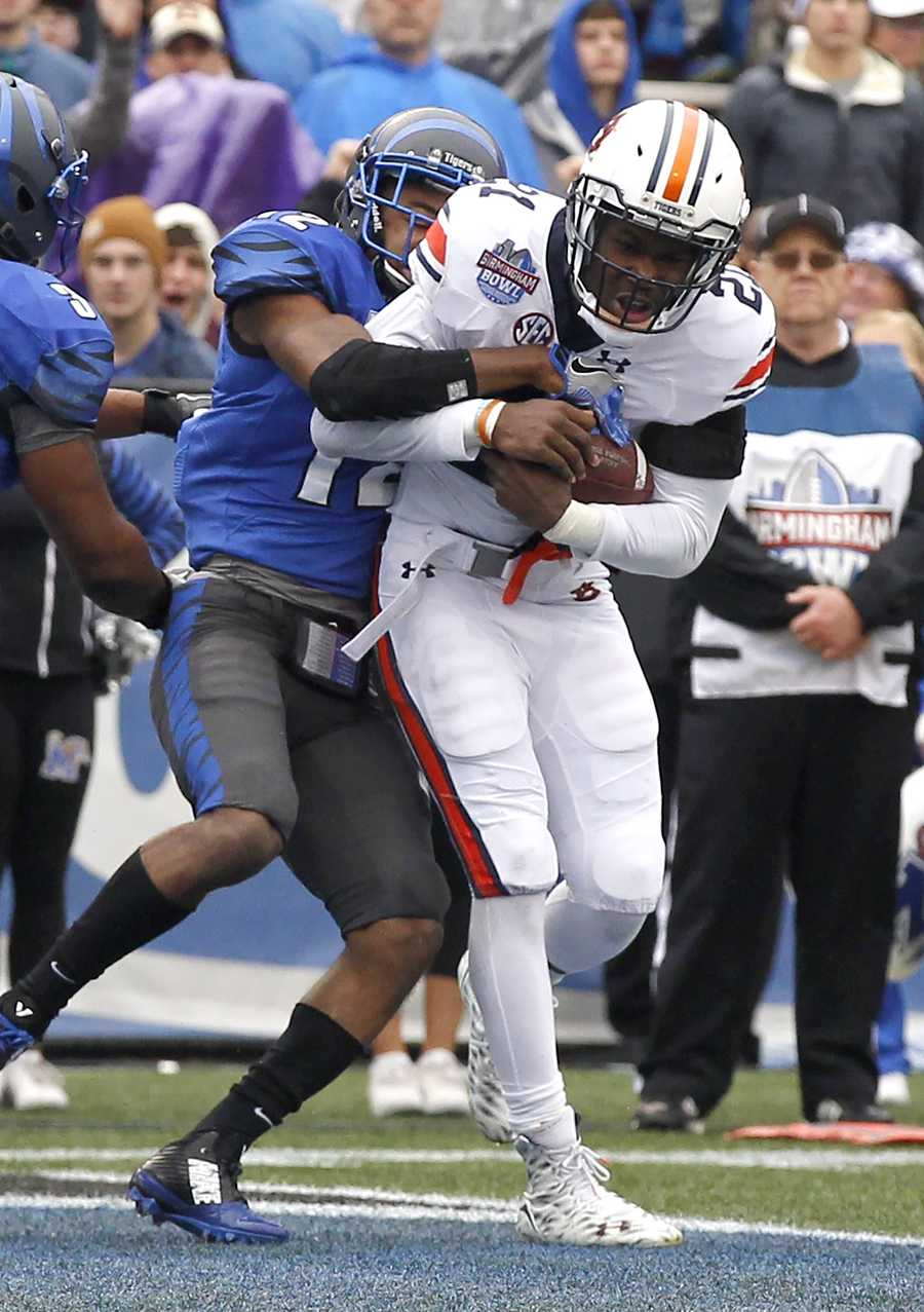 Auburn running back Kerryon Johnson (21) scores a touchdown as Memphis defensive back Chauncey Lanier (12) tries to tackle him during the first half of the Birmingham Bowl NCAA college football game, Wednesday, Dec. 30, 2015, in Birmingham, Ala.