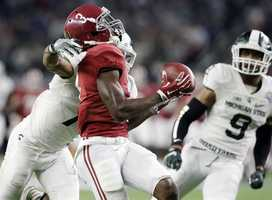 Alabama wide receiver Calvin Ridley makes a 50-yard reception over Michigan State defensive back Demetrious Cox (7) during the first half of the Cotton Bowl NCAA college football semifinal playoff game against Michigan State, Thursday, Dec. 31, 2015, in Arlington, Texas.