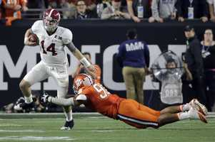 Alabama's Jake Coker (14) gets away from Clemson's Kevin Dodd during the first half of the NCAA college football playoff championship game Monday, Jan. 11, 2016, in Glendale, Ariz