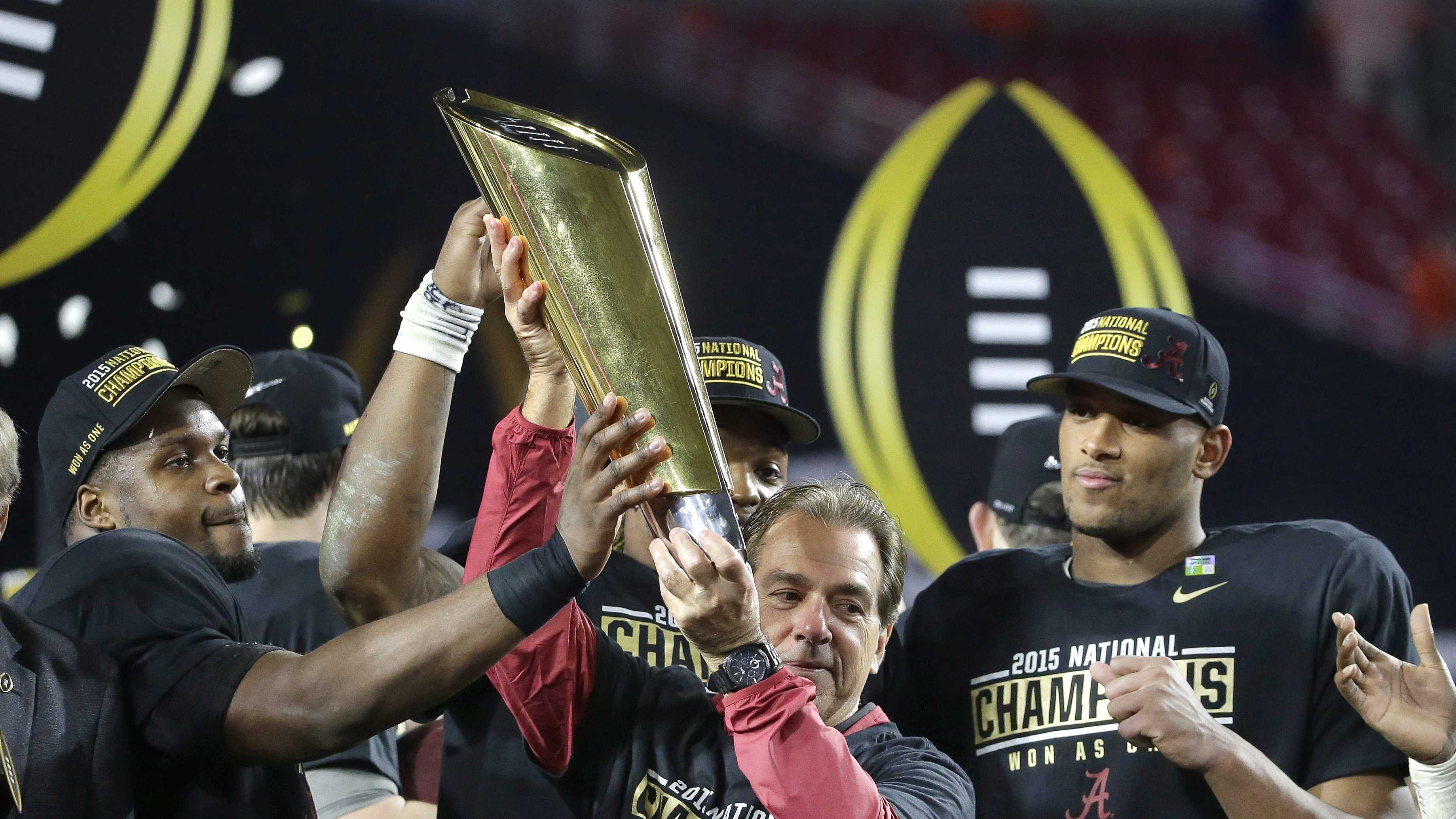 Alabama head coach Nick Saban, center, holds up the championship trophy with players after the NCAA college football playoff championship game against Clemson Monday, Jan. 11, 2016, in Glendale, Ariz. Alabama won 45-40.