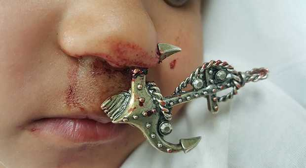 Boy with hook necklace in his nose.