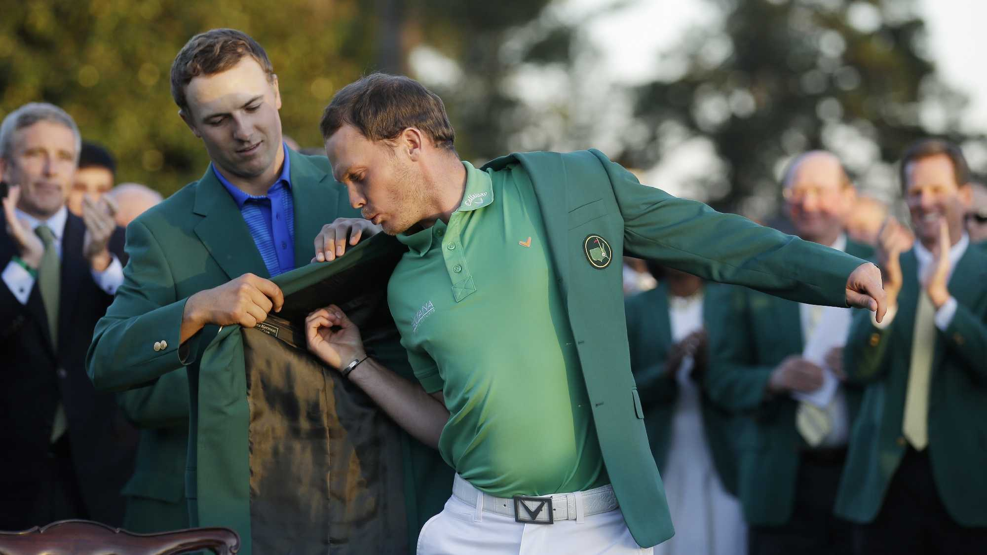 Defending champion Jordan Spieth, left, helps 2016 Masters champion Danny Willett, of England, put on his green jacket following the final round of the Masters golf tournament Sunday, April 10, 2016, in Augusta, Ga.